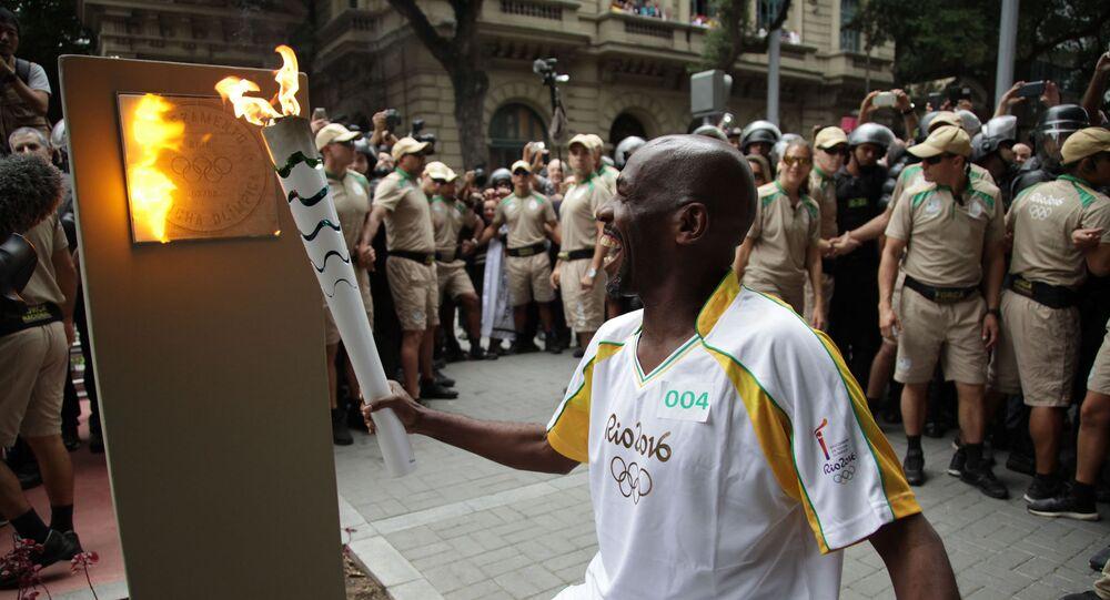 Cercado de seguranças, o carismático gari Renato Sorriso acende o primeiro dos cinco marcos olímpicos da cidade do Rio