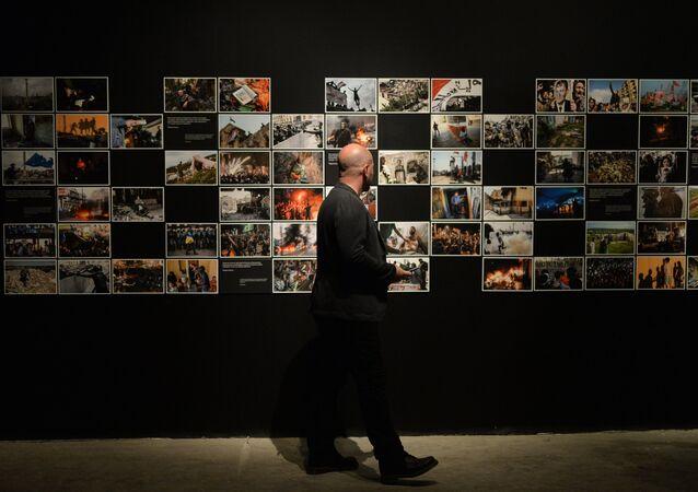Visitante na exposição de fotos que foram premiados no Concurso Jornalístico Fotográfico Internacional Andrei Stenin 2015, Moscou, Rússia