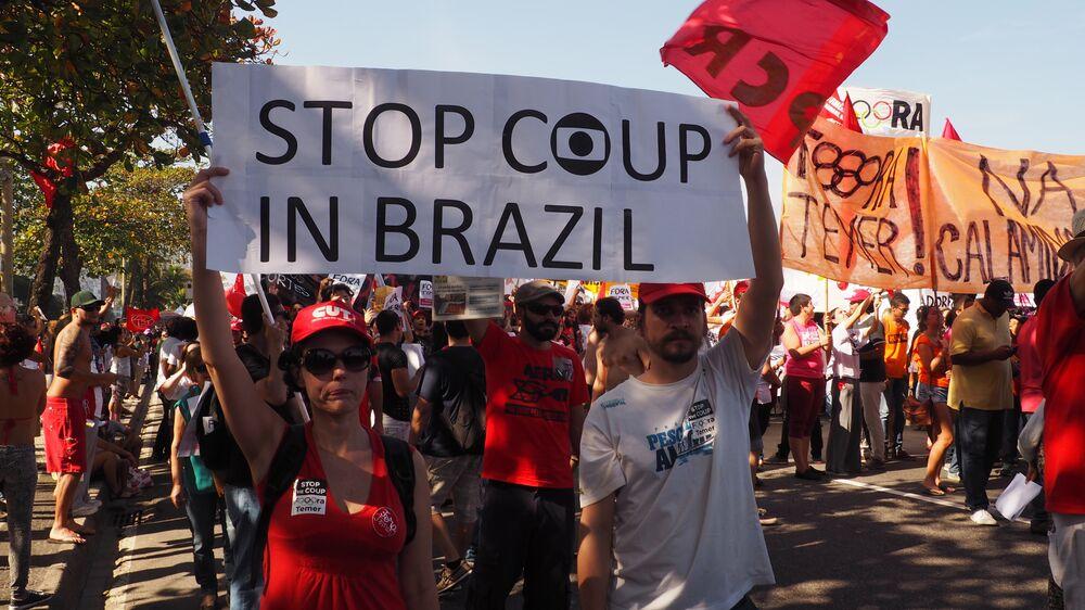 Manifestantes carregam cartazes em inglês contra o golpe no Brasil