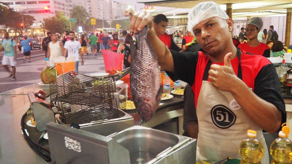 Vendedor frita peixe em quiosque de Copacabana