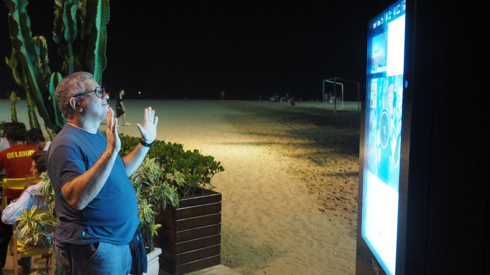 Homem tira selfie em câmera pública instalada na praia de Copacabana