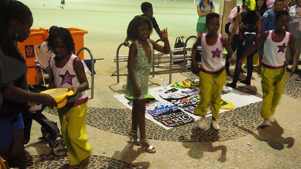 Crianças sambam na orla de Copacabana para atrair turistas