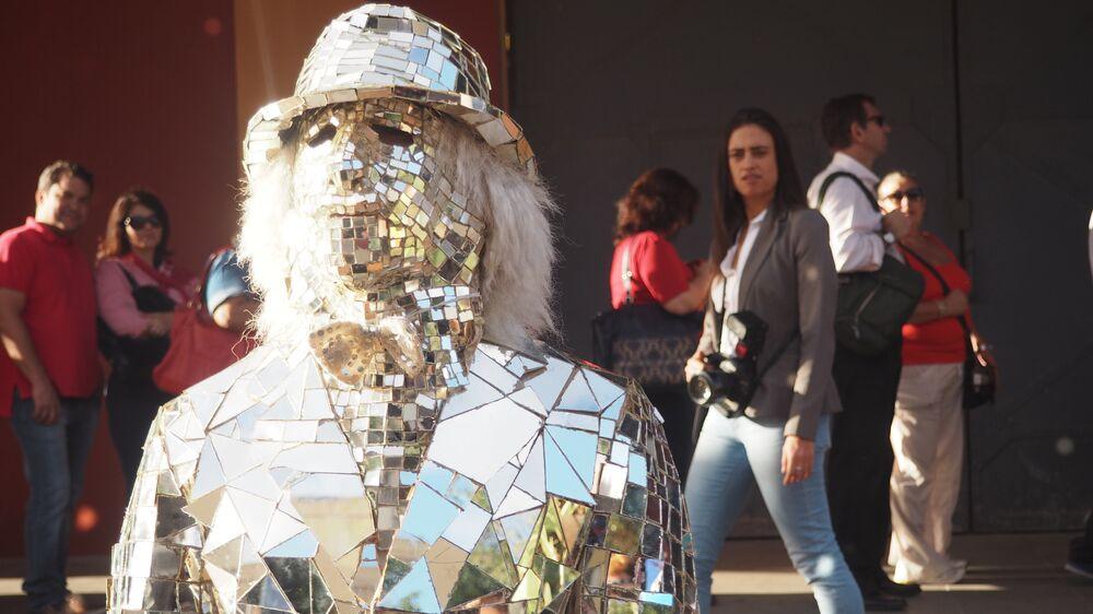 Homem-espelho tira fotos com turistas em frente à Casa Brasil