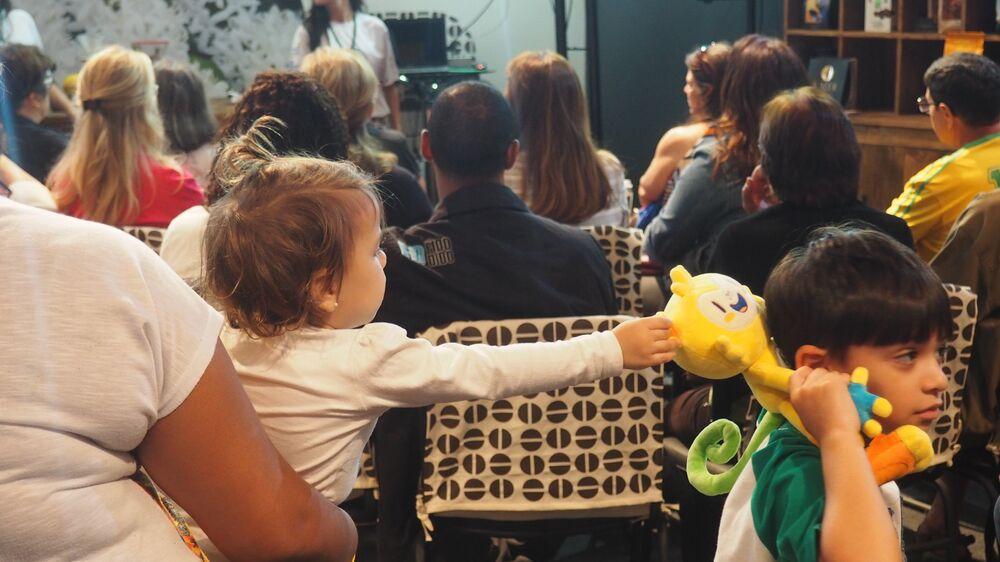 Bebê tenta pegar mascote da Rio 2016 dos ombros do irmão na Casa Brasil