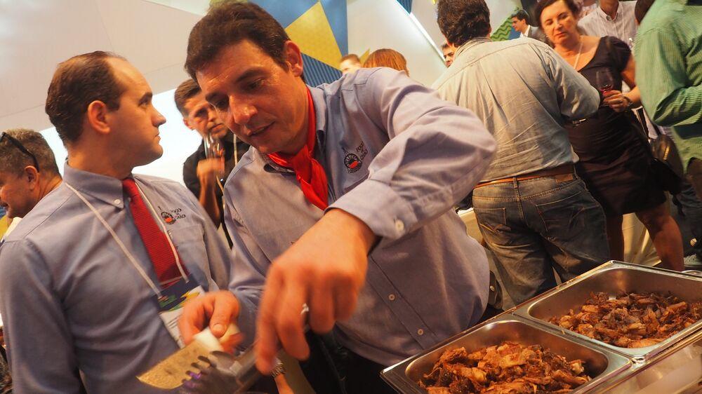 Garçom serve churrasco brasileiro para visitantes na Casa Brasil