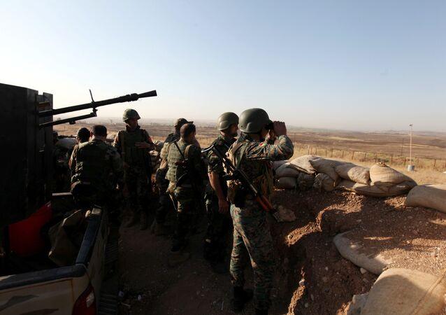 Forças curdas Peshmerga observam aldeia perto da cidade de Mossul no Iraque, 29 de maio 2016