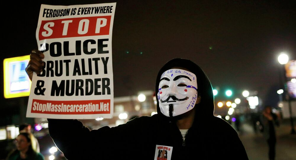 A protestor wearing a Guy Fawkes mask holds a sign as demonstrators march through the streets of Ferguson, Missouri, March 12, 2015