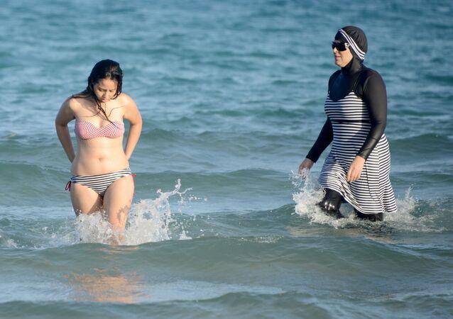 Uma mulher em burquíni se diverte no mar junto com uma mulher em maiô comum, em 16 de agosto de 2016, em uma praia perto de Tunis, na Tunísia