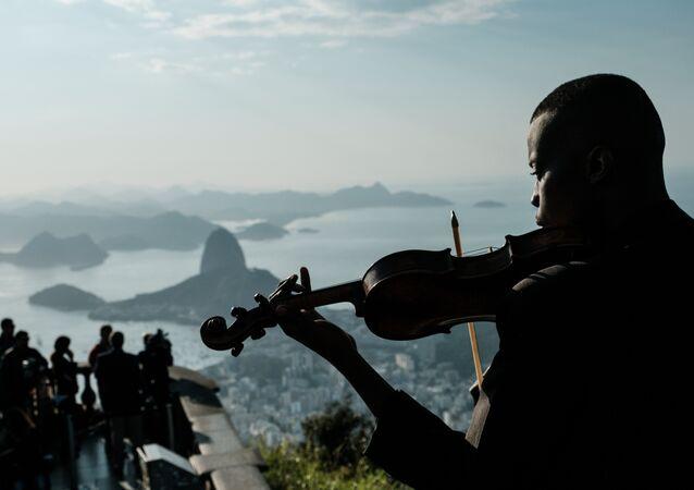 Um membro do conjunto Fino da Música toca violino na frente do Cristo Redentor, no Rio de Janeiro