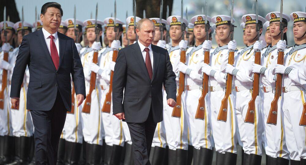 Presidente chinês Xi Jinping e o presidente russo Vladimir Putin na cerimônia de abertura de exercícios navais sino-russos na base marítima chinesa em Xangai, China, 2014  (foto de arquivo)