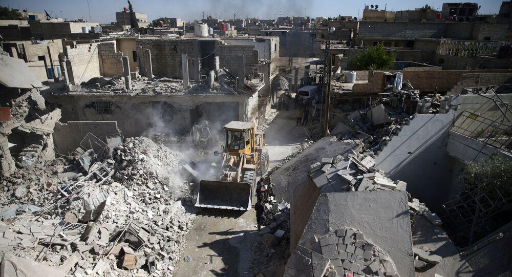 Carregador frontal removendo destroços em sítio atacado pela aviação em Douma, Damasco (foto de arquivo)