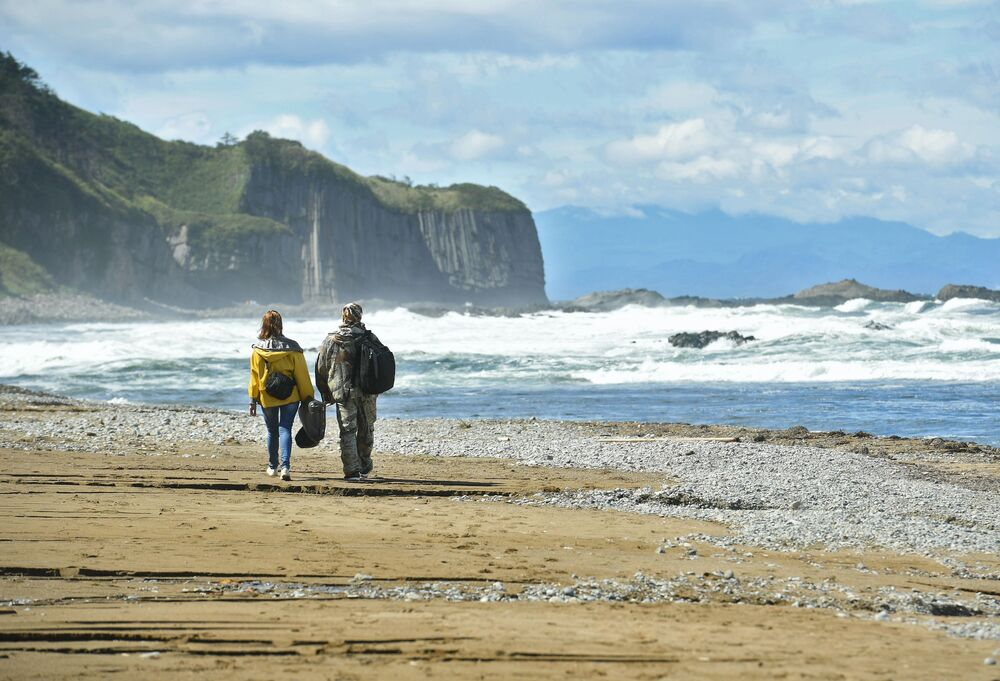 Turistas na costa do mar de Okhotsk, na ilha Kunashir