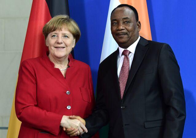 A chanceler alemã, Angela Merkel, aperta a mão do presidente do Níger, Mahamadou Issoufou