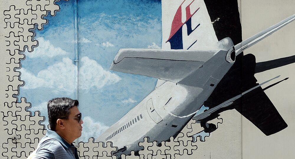 Homem passeia perante a muralha com a imagem do avião desaparecido Boeing 777 da Malaysia Airlines, Shah Alam, Malásia, março de 2016