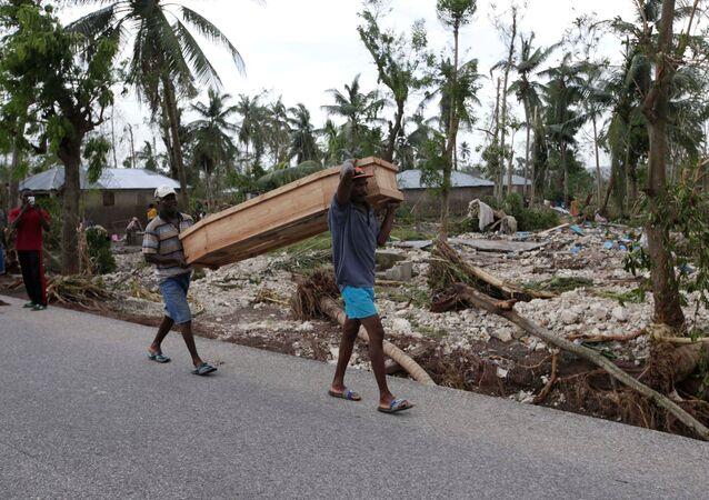 Homens carregam caixão com vítima do furacão Matthew no Haiti, 6 de outubro de 2016