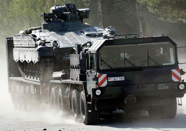 A transportation truck carries an armoured transport vehicle during a demonstration event held for the media by the German Bundeswehr.