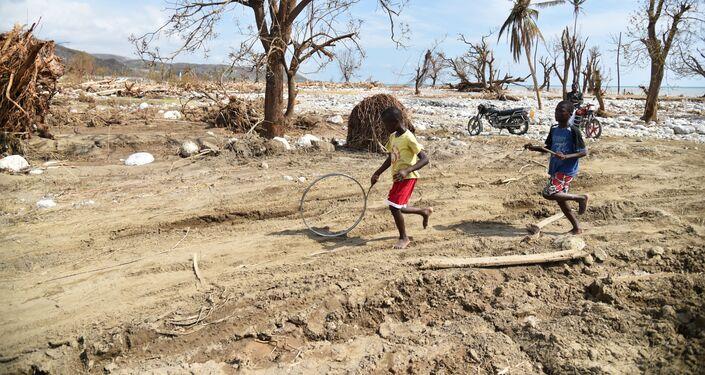 Meninos empurram um pneu entre as ruínas da cidade de Les Cayes (Haiti), afetada pelo furacão Matthew