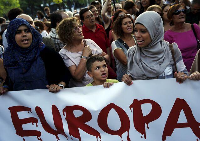 Participantes de uma manifestação que demanda uma mudança na política europeia em relação aos refugiados, Madri, Espanha