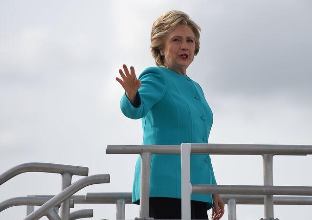 Presidenciável democrata Hillary Clinton acena com a mão no seu dia de anos no aeroporto internacional de Maiami, EUA, 26 de outubro de 2016