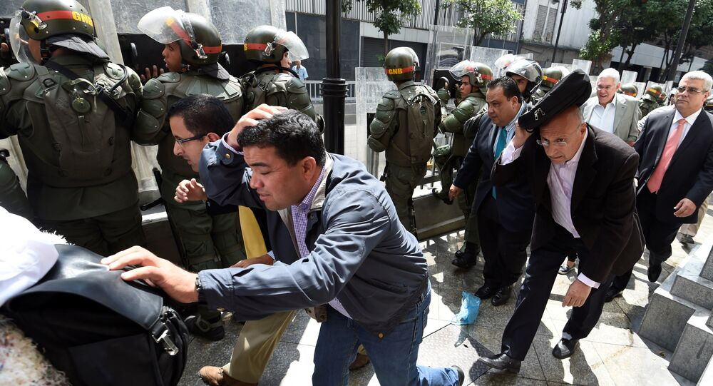 Parlamentares da oposição venezuelana se protegem enquanto tentam chegar à Assembleia Nacional em Caracas, 27 de outubro de 2016.