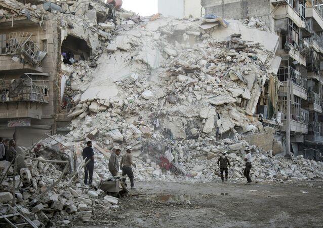 Membros do grupo conhecido como Capacetes Brancos procuram por vítimas perto do edifício destruído no resultado de ataque aérea no norte de Aleppo. 17 de outubro, 2016