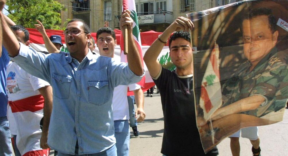 Estudantes libaneses mostram um cartaz com a foto de Michel Aoun junto com a bandeira nacional (foto de arquivo)