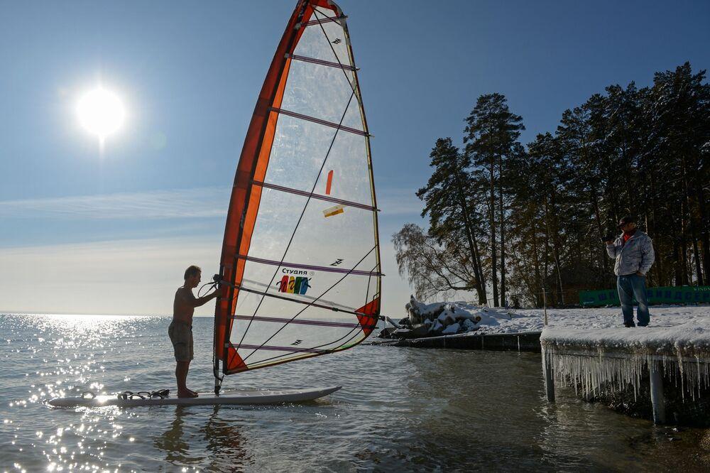 Atleta Aleksandr Orlov (à esquerda) pratica windsurf, sob a temperatura de 5 graus negativos