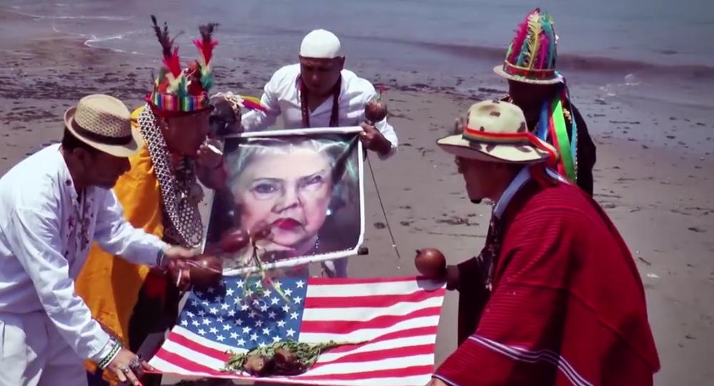 Xamãs peruanos realizam ritual na praia do Pacífico no Peru exibindo foto de Hillary Clinton e bandeira dos EUA