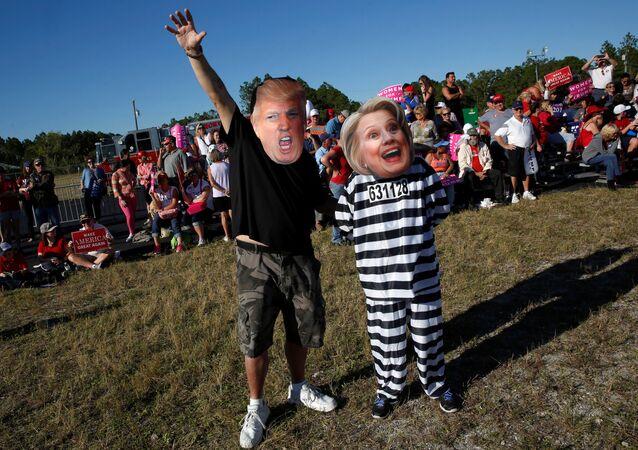 Homem com máscara de Donald Trump ao lado de mulher com máscara de Hillary Clinton, vestida para a prisão, em comício do republicano na Flórida, 23 de outubro de 2016