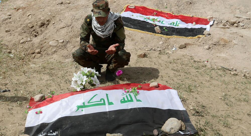 Um miliciano xiita reza em frente a uma cova onde se acredita estar o corpo de um soldado iraquiano.