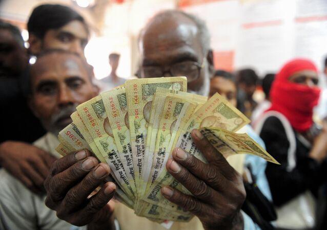Um homem indiano segura nas mãos várias notas de 500 rupias, que perderam seu valor nominal após uma reforma do governo de Narendra Modi