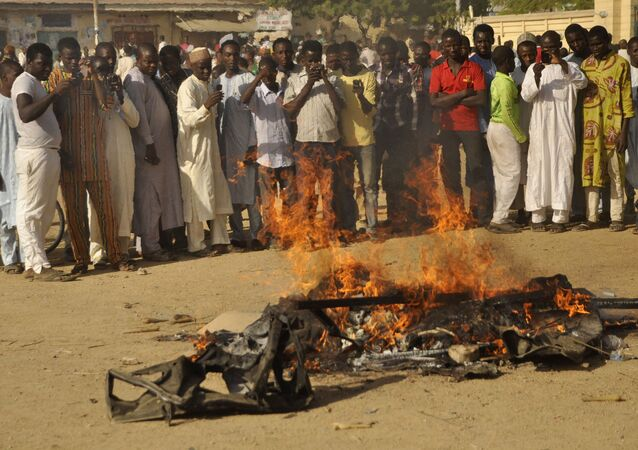 Multidão acompanha um pedaço de carro em chamas após uma explosão em 28 de novembro de 2014 em Kano, Nigéria; o local tinha sido alvejado pelo Boko Haram