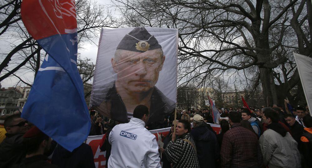 Manifestantes empunham o retrato do presidente russo Vladimir Putin durante um protesto contra a OTAN no centro de Belgrado, Sérvia, fevereiro de 2016