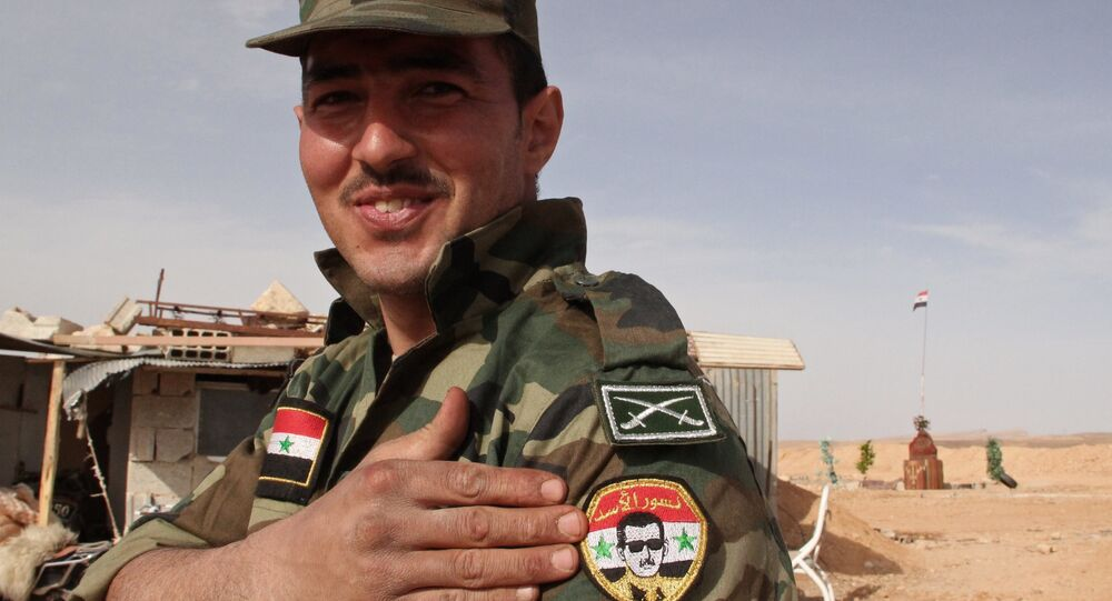 Soldado do Exército Sírio com o retrato do presidente Bashar Assad perto da fronteira líbano-síria