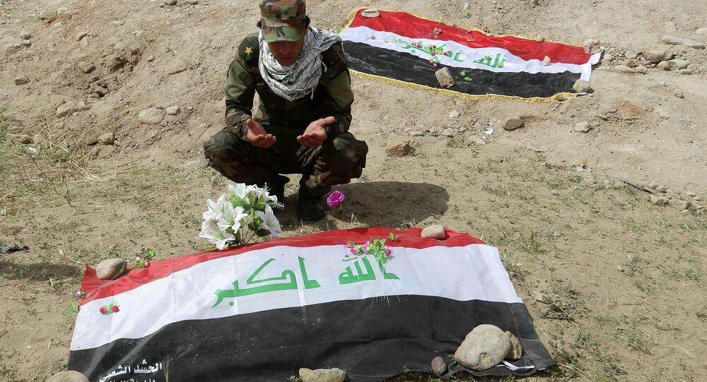 Soldado reza sobre cova coletiva no Iraque