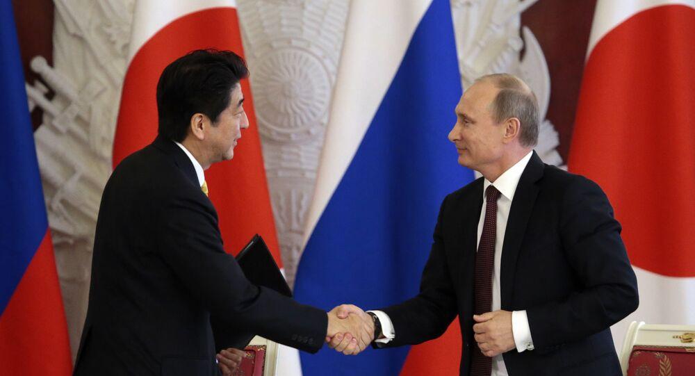 Premiê japonês Shinzo Abe apertando a mão do presidente russo Vladimir Putin