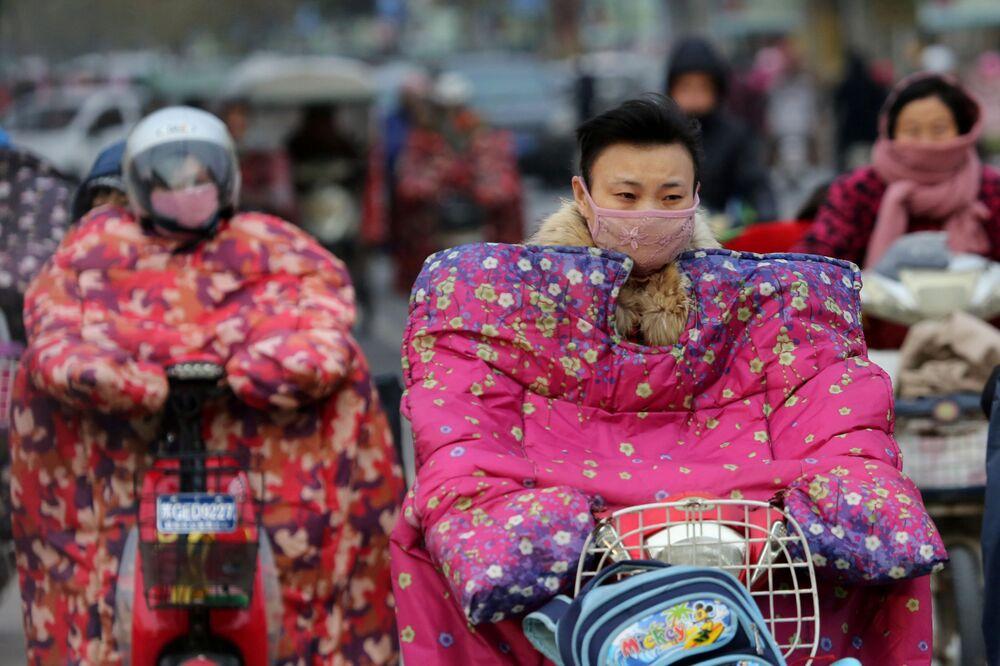 Ciclistas chineses vestem jaquetas especiais para se proteger do vento gelado, 23 de novembro de 2016