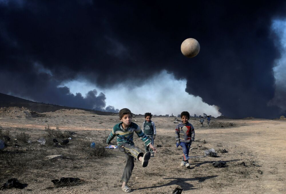 Crianças brincam com uma bola ao sul de Mossul