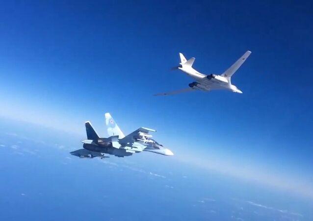 O caça Su-30SM da Força de Defesa Aeroespacial russa escolta um bombardeiro Tu-160 que disparou mísseis de cruzeiro contra os alvos do Daesh na Síria