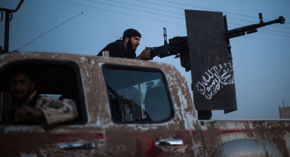 Um membro do agrupamento terrorista  Ahrar al-Sham despara contra os combatentes das YPG, na província de Raqqa, em 25 de agosto de 2013