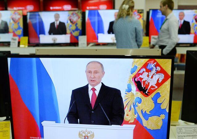 Transmissão do discurso do presidente russo Vladimir Putin perante o parlamento russo no Kremlin, em uma das lojas de eletrônicos na cidade russa de Omsk, Rússia, 1 de dezembro de 2016
