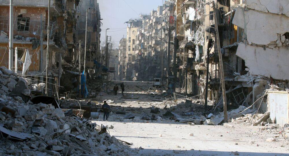 Os sírios andam pelas ruas com prédios desmoronados, ao fugirem aos confrontos entre as forças do governo e os rebeldes, no Leste de Aleppo