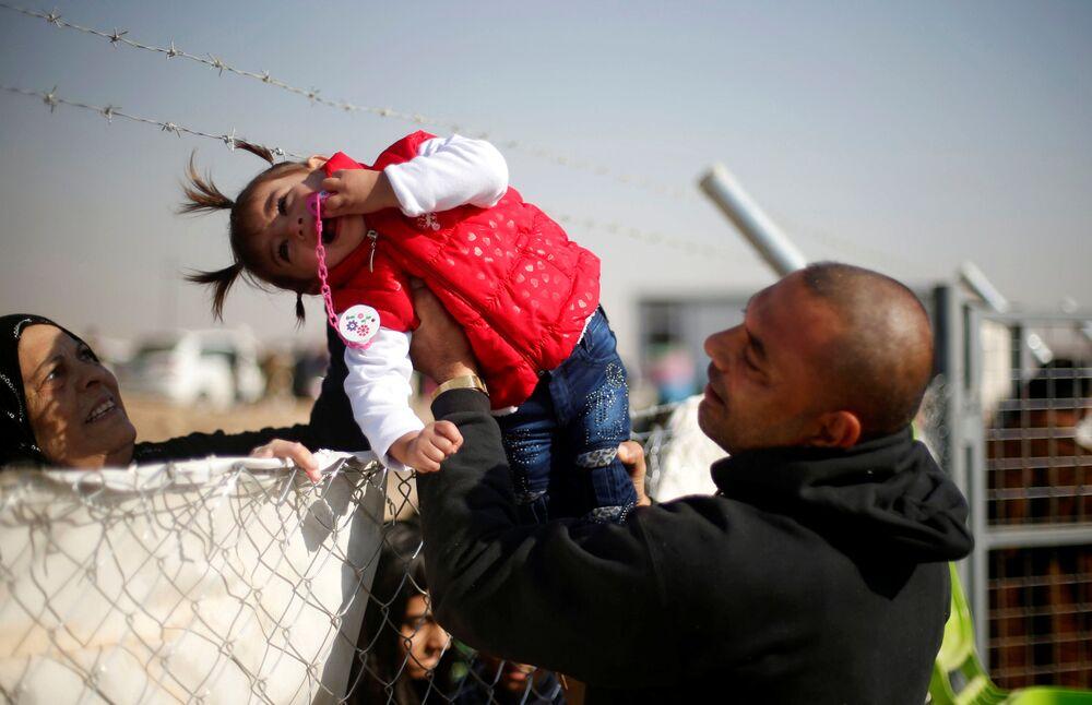 Homem que fugiu do território controlado por terroristas em Mossul passa sua filha à avó através da cerca