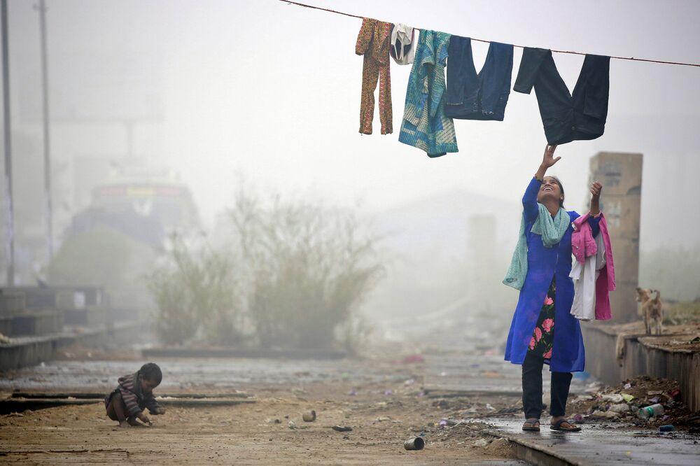 Mulher recolhe roupa durante nevoeiro forte em Nova Delhi, Índia