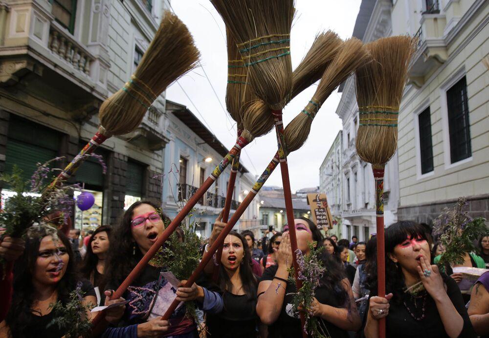 Mulheres com vassouras durante marcha contra violência de gênero em Quito, Equador