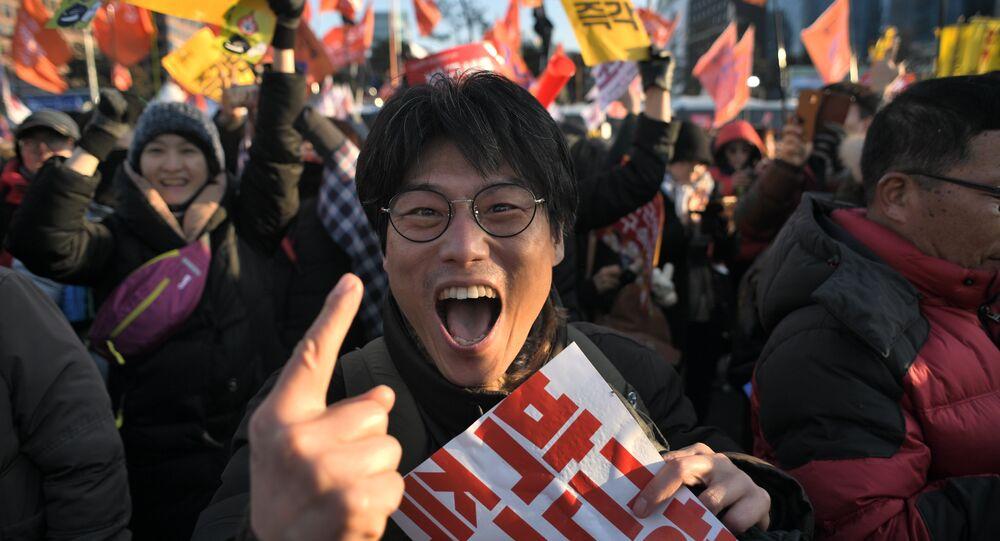 Um manifestante reage após o impeachment bem sucedido do parlamento sul-coreano da presidente Park Geun-hye enquanto multidões se juntam fora da Assembleia Nacional em Seoul em 9 de dezembro de 2016.