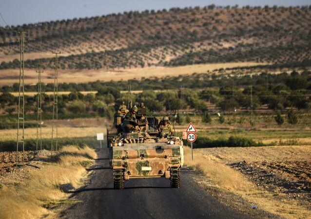 Soldados turcos estão em cima de tanque do exército turco de volta para a Turquia da cidade fronteiriça sírio-turca de Jarabulus em setembro na cidade fronteiriça turco-síria de Karkamis