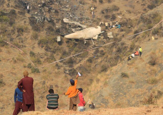 Paquistaneses no local de queda de avião, aldeia de Saddha Batolni, Paquistão (imagem referencial)