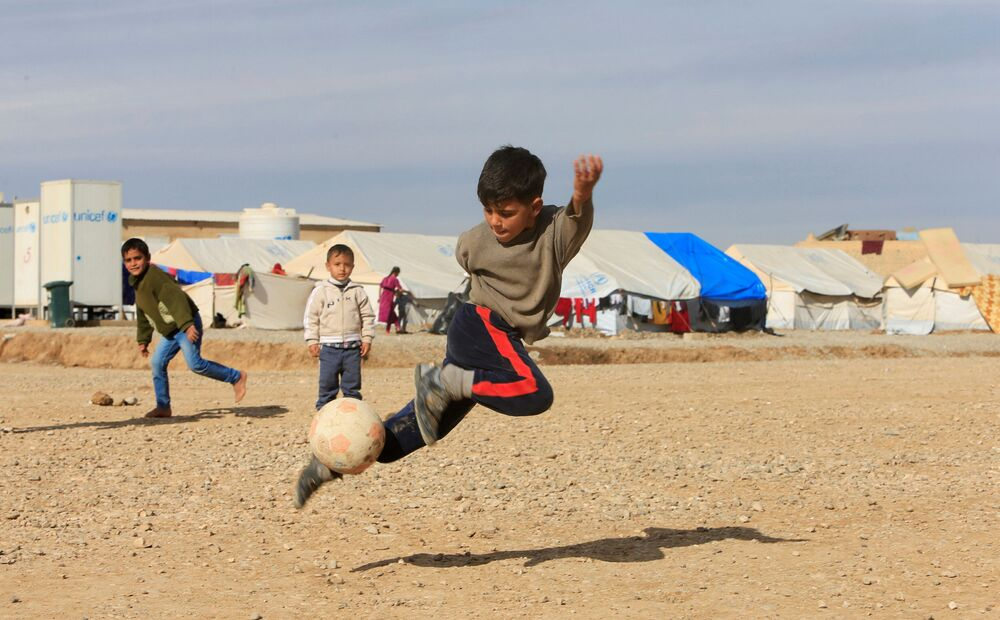 Meninos jogam bola em campo de refugiados no Iraque