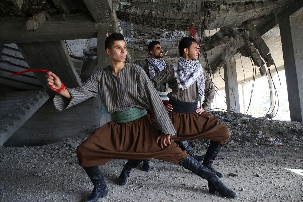 Dançadores palestinos executam dança tradicional Dabke em prédio destruído pela guerra entre Israel e Hamas